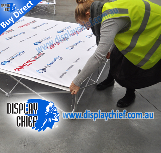 Fitting and tightening adjusting the fabric printing for the sign wall ready to stand upright